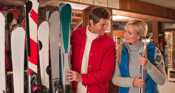 A happy couple stand in a ski shop looking at snowboarding and skiing equipment.