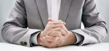 Businessman at desk in business job interview with hands clasped, attentive and listening in anticipation