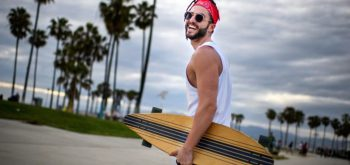 Male hipster person having fun on the beach with longboard skateboard.